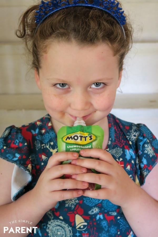 Girl eating applesauce pouch