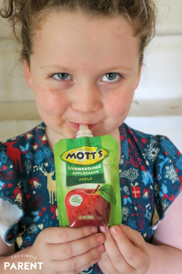 Girl eating Mott's applesauce pouch