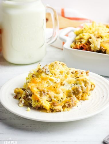 Breakfast casserole on a white plate with a glass of milk