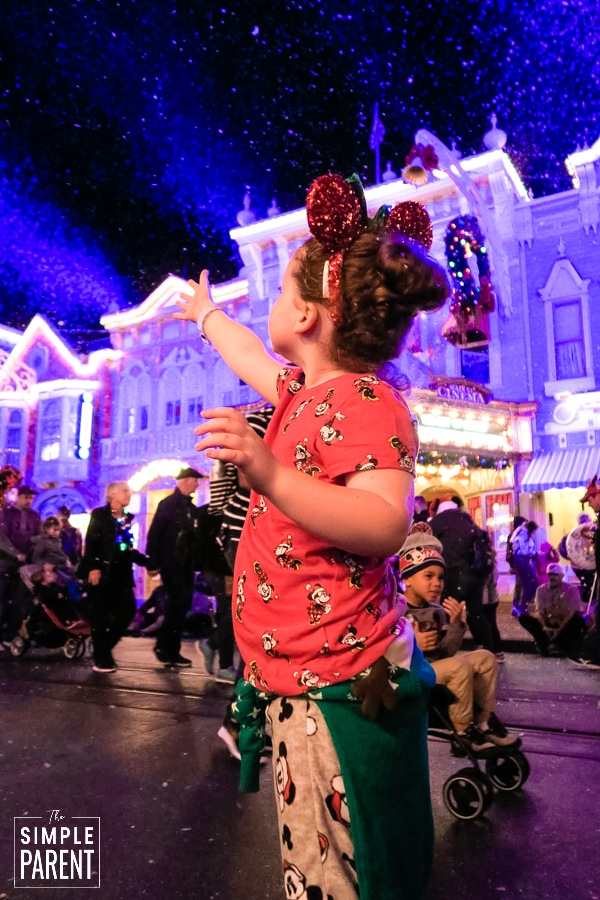 Girl wearing Christmas pajamas standing on Main Street USA at Disney World