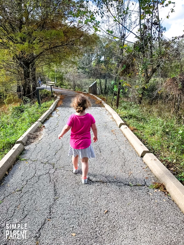 Young girl walking down a path in a forest