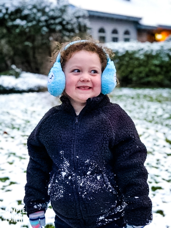 Girl wearing earmuffs a winter coat in front of a snowy yard