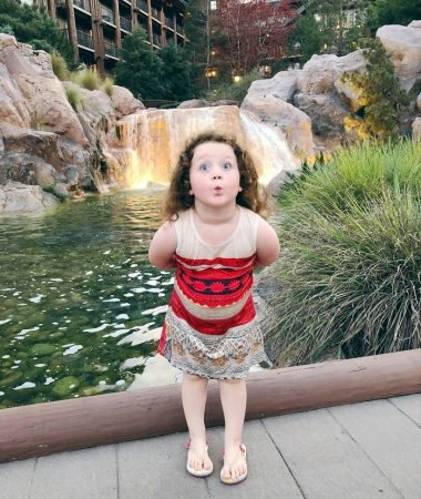 Little girl posing in front of waterfall.