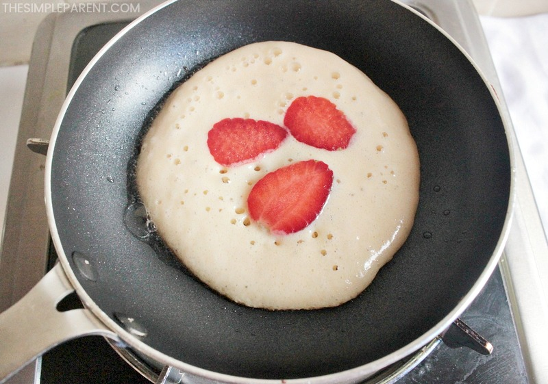 Add strawberry slices to pancakes.