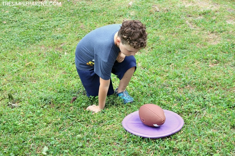 Boy trying field day ideas with a football.