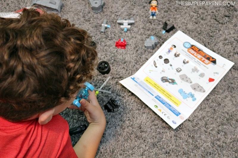 Boy building Rusty Rivets toys set.