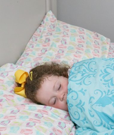 Girl taking a nap as part of toddler bedtime and nap routine.