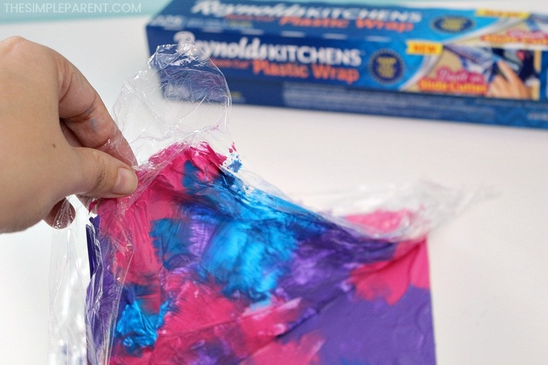 Removing plastic wrap to make cling wrap art for kids.