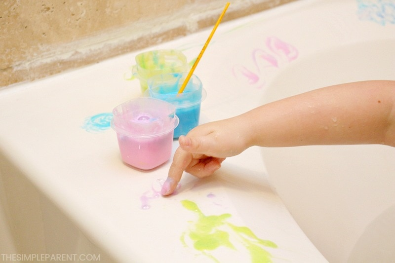 Child using kids bath paint to fingerpaint in the bath tub.