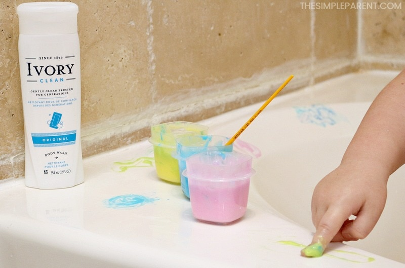 Kids finger painting in bath tub.
