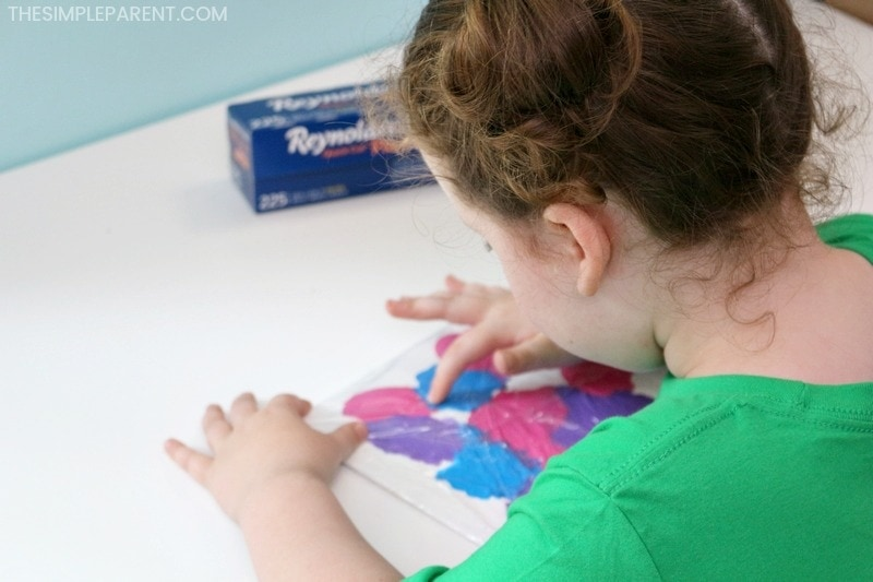 Child making a plastic wrap painting.