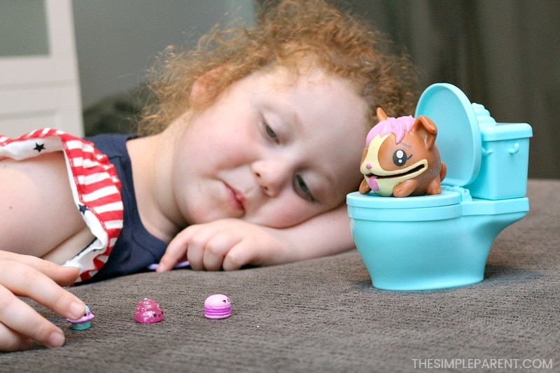 Girl playing with Pooparoos Surpriseroos collectible toys.