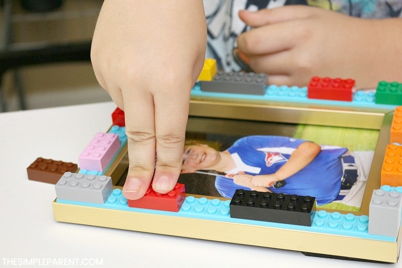 Child building with Lego blocks to make Lego Picture Frame craft.