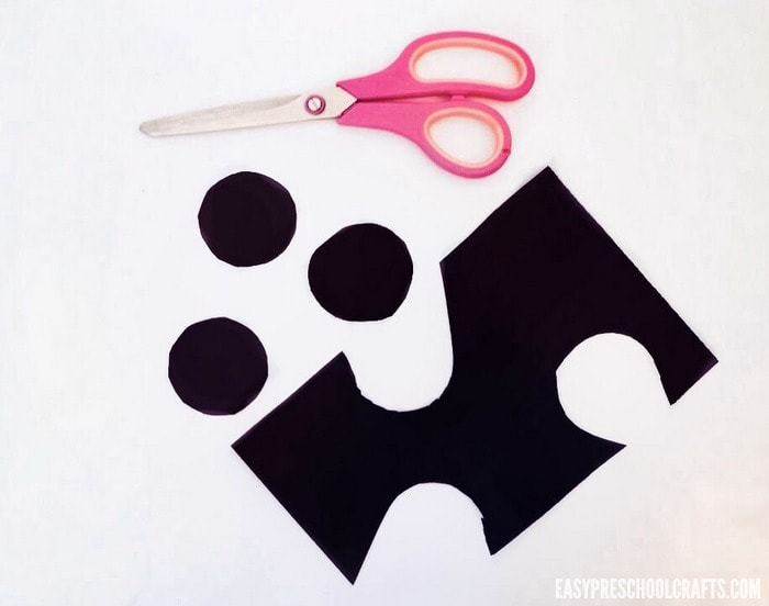 Cutting black circles out of construction paper