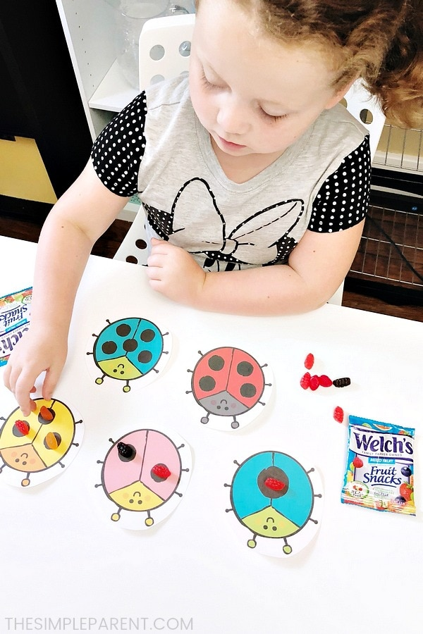Girl practicing numbers with ladybug number worksheets for kindergarten