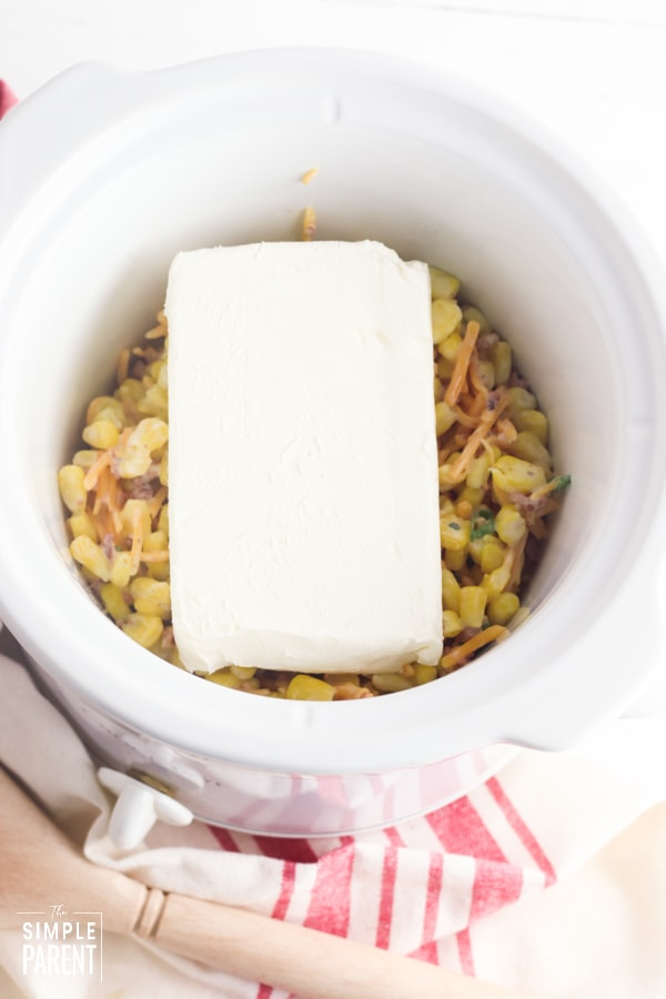 Block of cream cheese on top of bacon corn dip in a Crockpot slow cooker