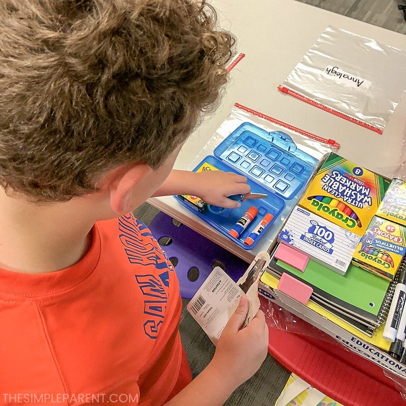 Student sorting school supplies for Back to School