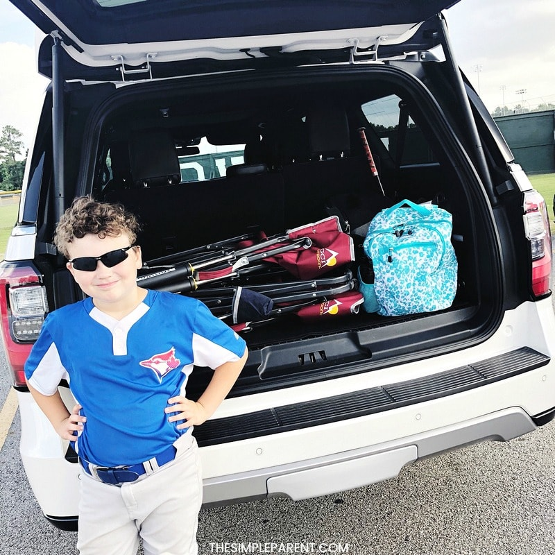 Boy standing outside family car
