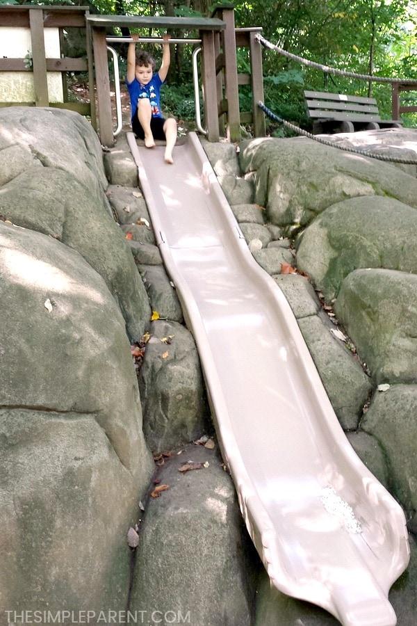 Preschool boy sliding down a big slide