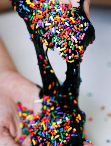 Making black slime with paint and sprinkles