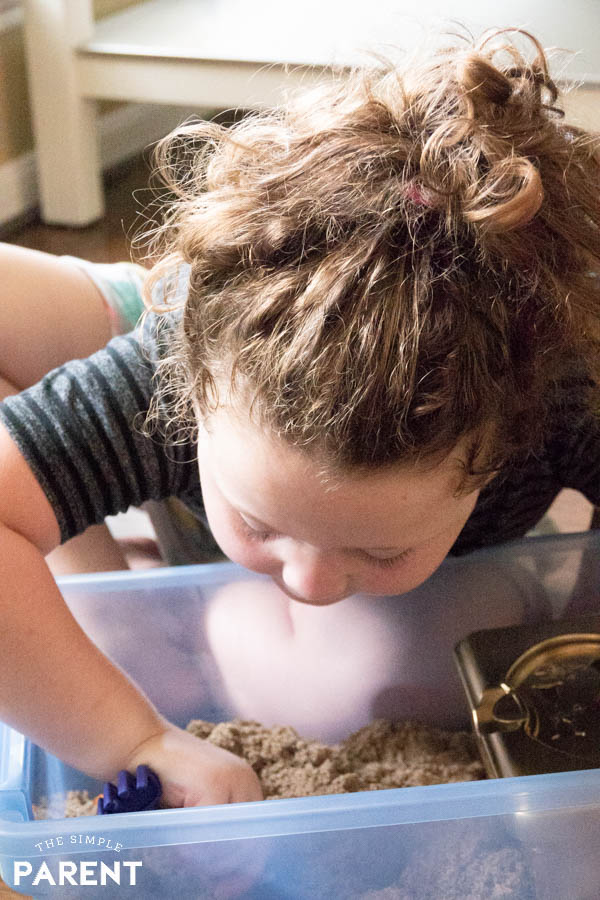Girl playing in DIY treasure chest sensory box