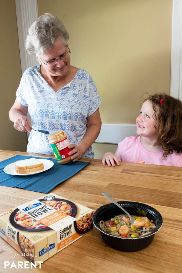 Grandmother and granddaughter making meal
