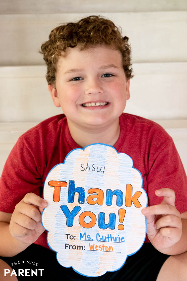 Boy holding a teacher thank you note