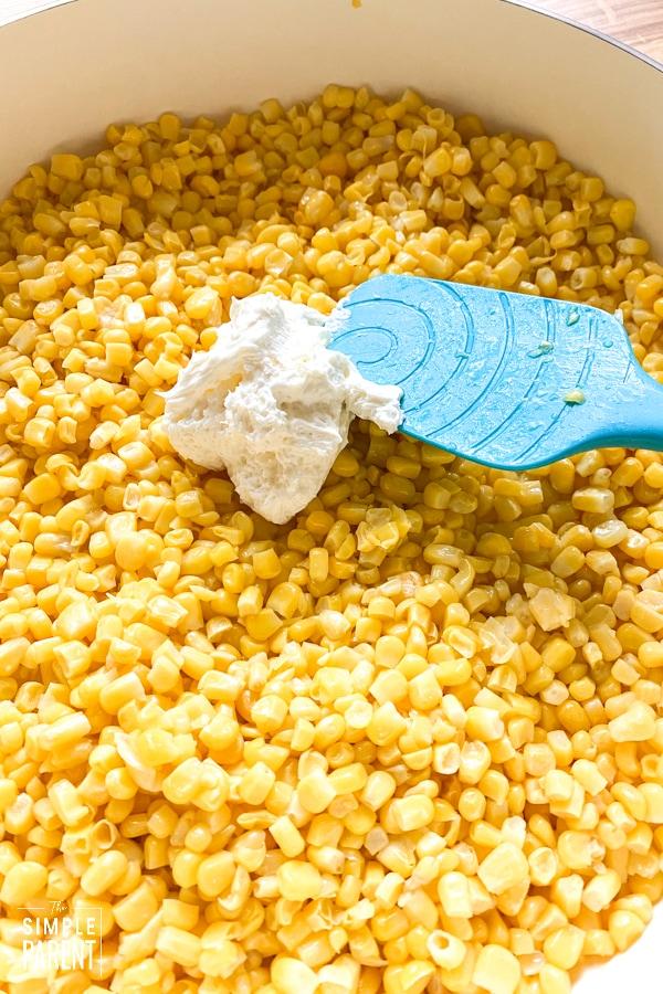 Spatula mixing cream cheese into corn in a pan