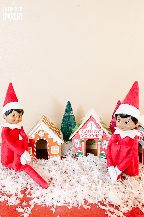 Boy and Girl Elf on Shelf sitting with small gingerbread looking houses