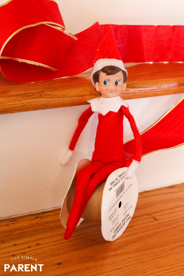 Elf rolling ribbon down the stairs