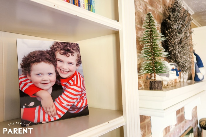 Photo of kids on shelf next to fireplace mantle in home
