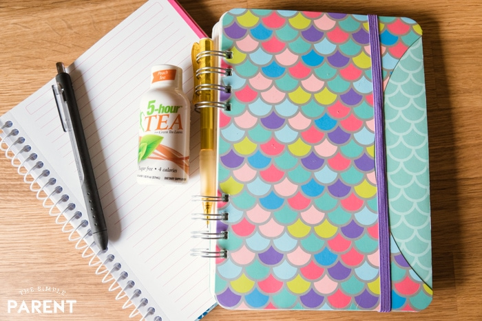 Energy drink, notebook, and planner on table