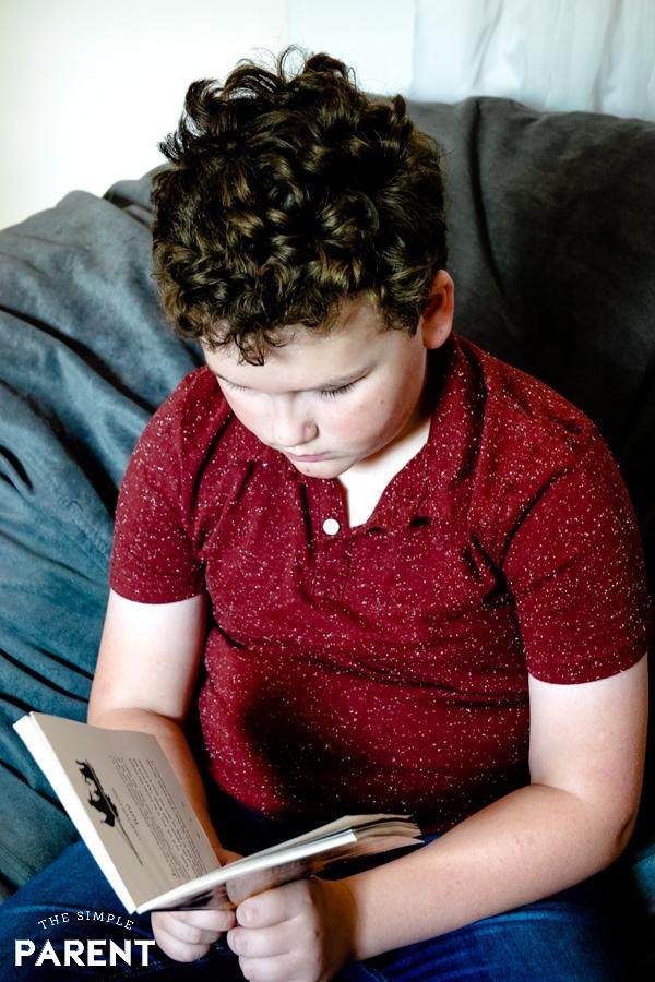 Boy reading Magic Treehouse book