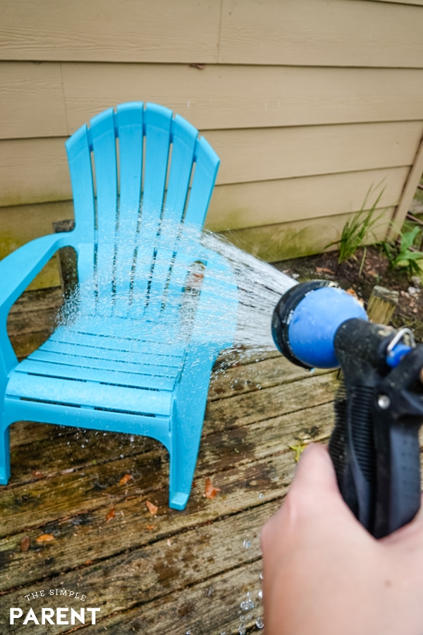Washing off a deck chair with a garden hose