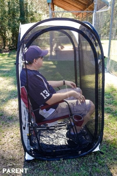 Baseball dad sitting in an Under the Weather pod at the baseball field