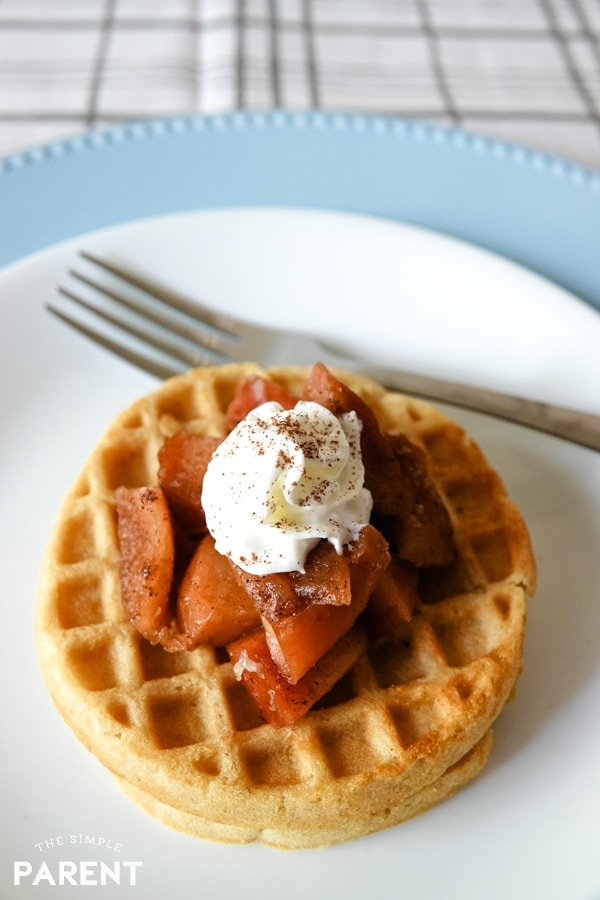 Crockpot cinnamon apples on waffle with whipped cream
