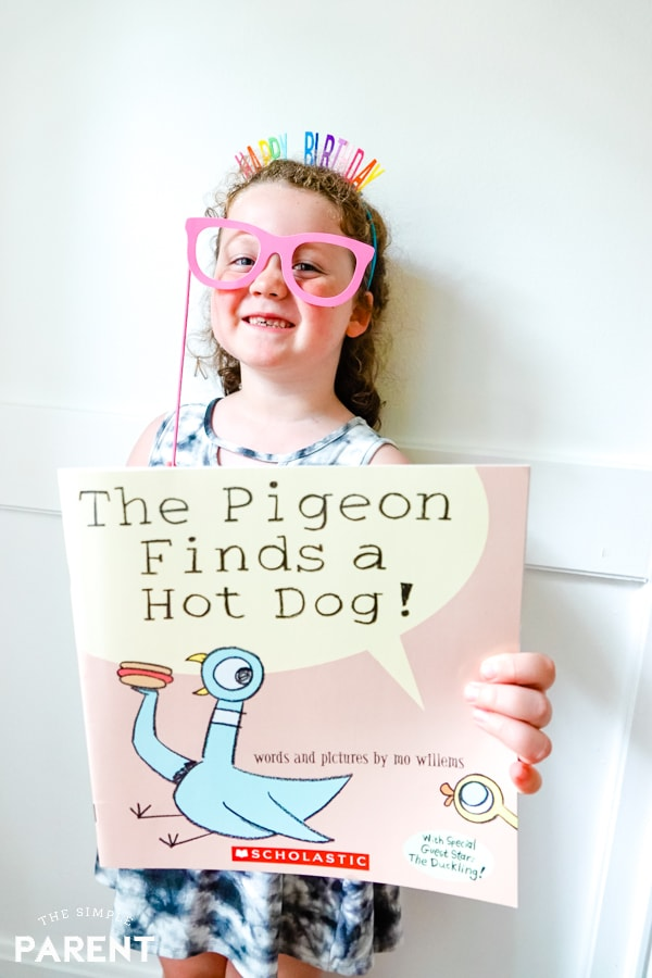 Girl holding The Pigeon Finds a Hot Dog! book by Mo Willems
