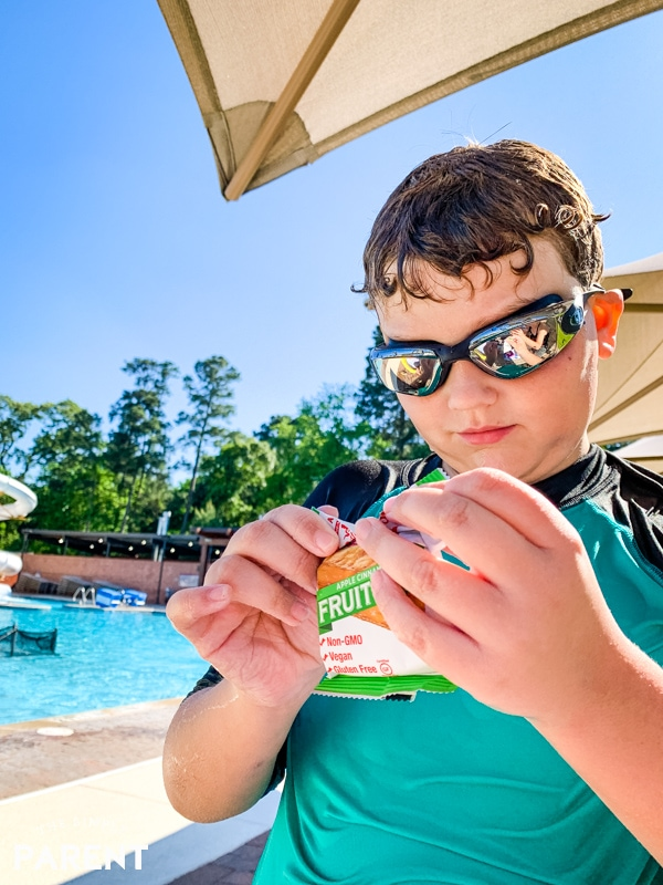 Boy opening pool snacks after swimming
