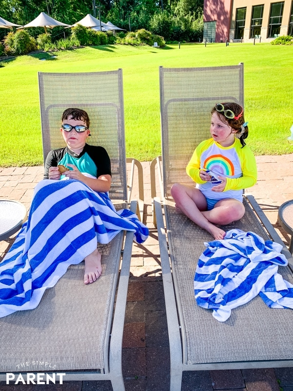 Kids sitting on lounge chairs by the pool
