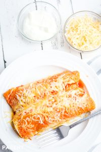 Plate of Crock Pot chicken enchiladas with sour cream and shredded cheese