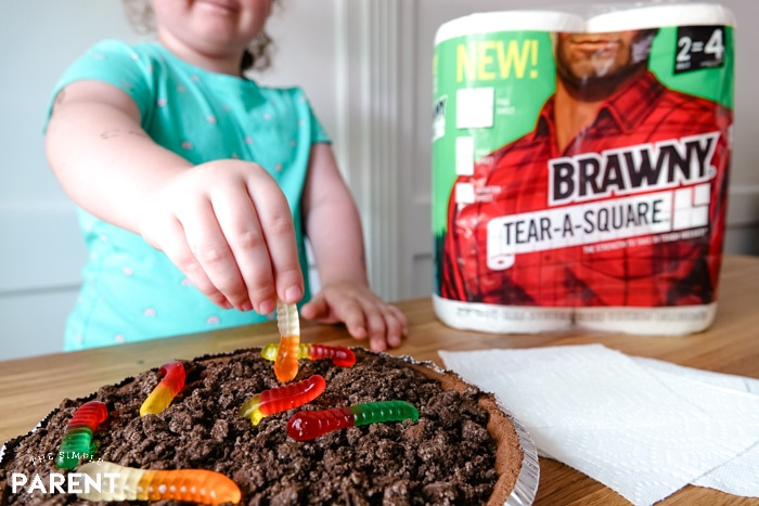 Child making mud pie with gummy worms