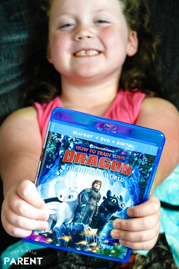 Girl holding How To Train Your Dragon 3 DVD
