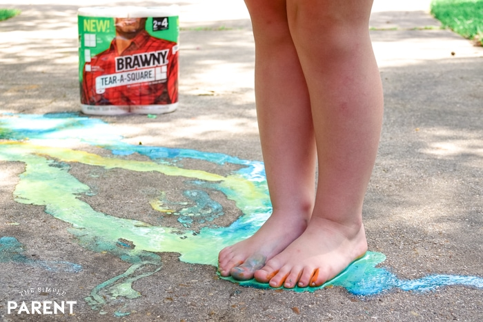 Child standing in sidewalk chalk paint on the driveway