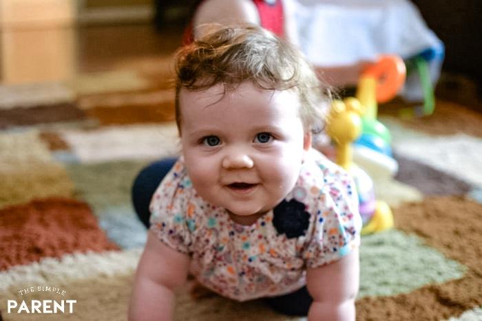 Baby girl smiling as she crawls