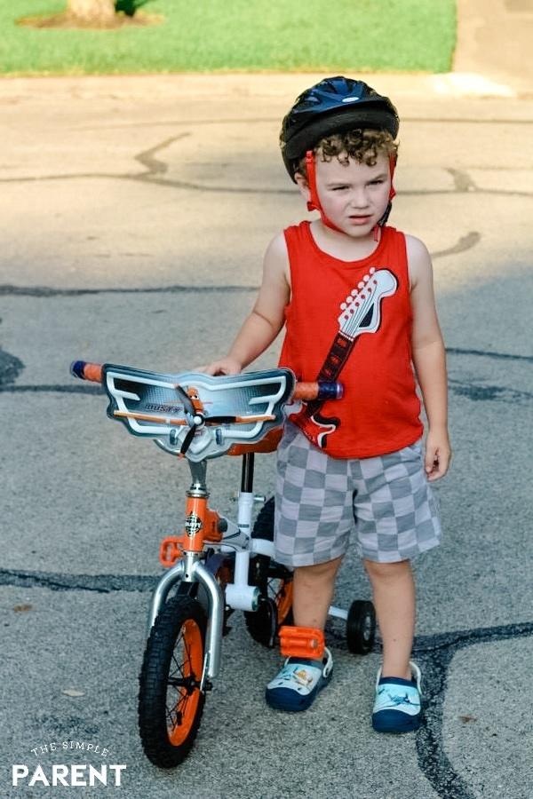 Toddler boy standing next to his bike