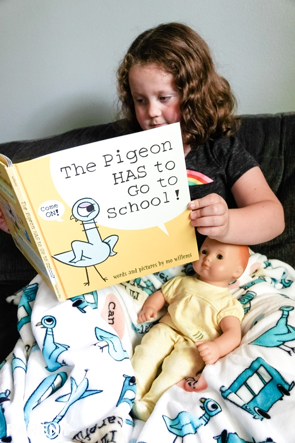 Girl reading The Pigeon HAS to Go to School book