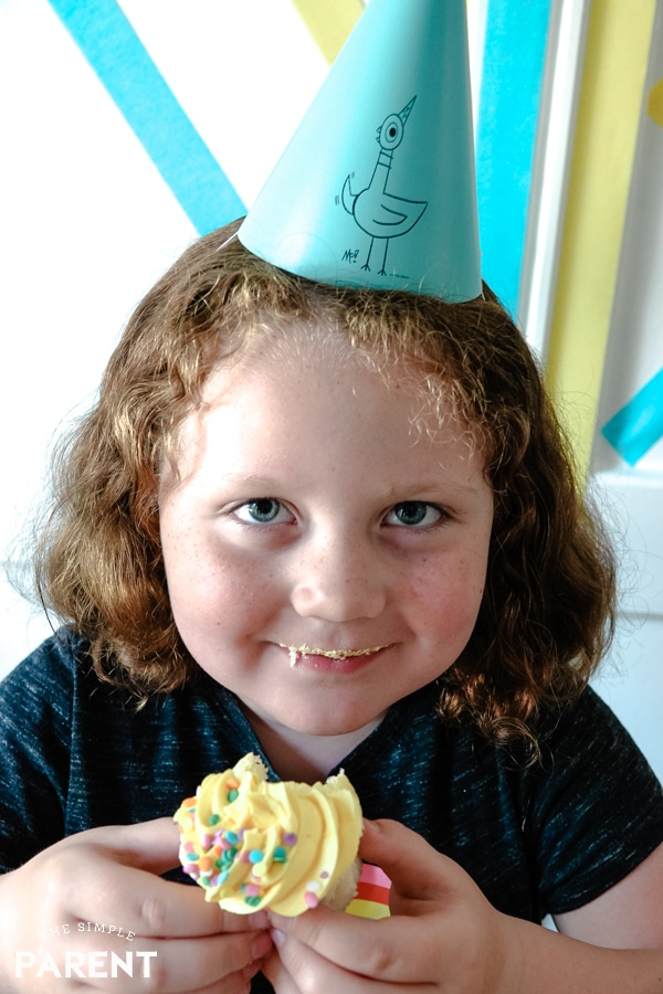 Girl eating a cupcake and wearing a party hat