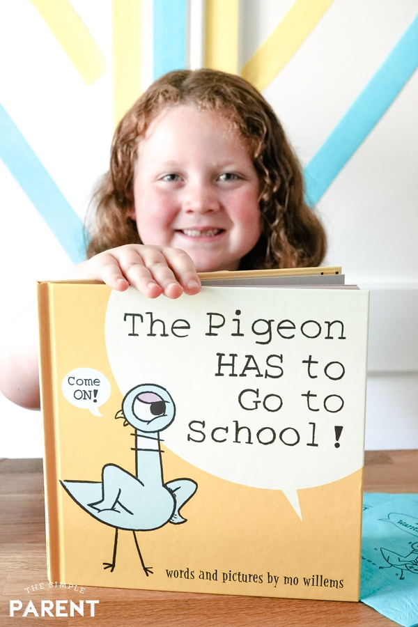 Girl holding The Pigeon HAS to Go to School book