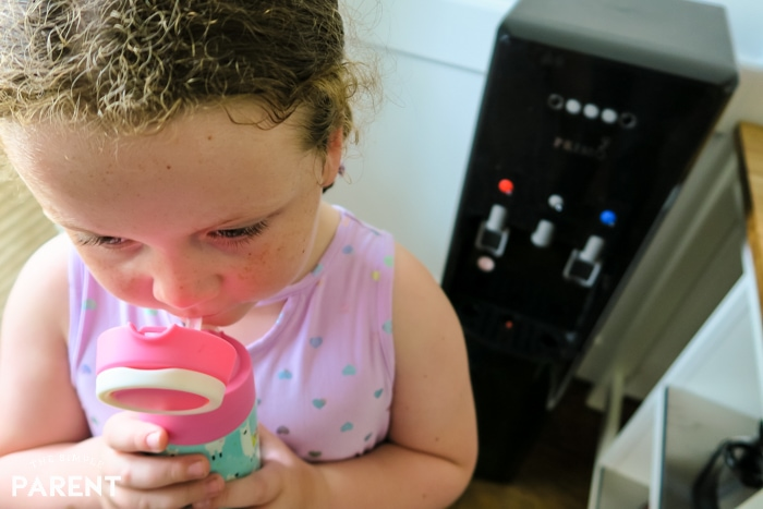Girl drinking from reusable water bottle in front of Primo water dispenser