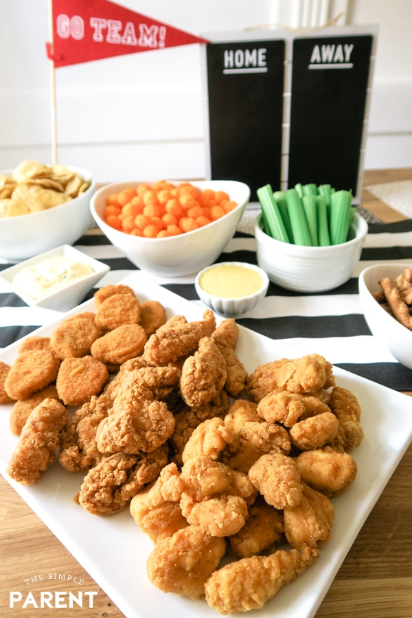 Chicken nuggets and chicken strips with celery sticks and cheese balls for game day.